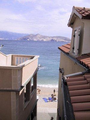 o. Krk - Baška - Baška a menší pláž před domy, v pozadí ostrůvek Prvić a pevnina s Velebitem (nahrál: iva2709)